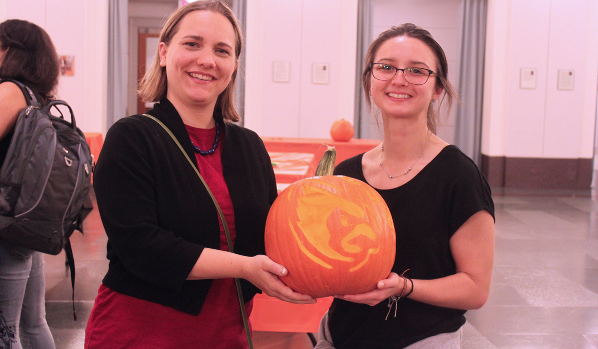 two students holding a carved pumpkin