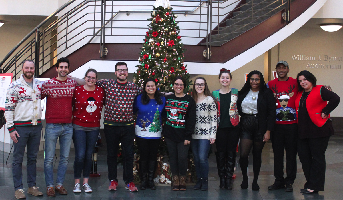 Law students and staff pose in Christmas sweaters in front of the law school's Christmas tree in the atrium